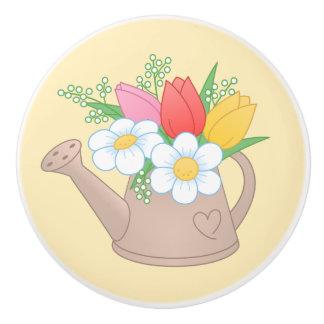 Regadera del jardín con las flores en amarillo pomo de cerámica