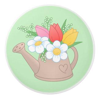 Regadera del jardín con las flores en verde pomo de cerámica