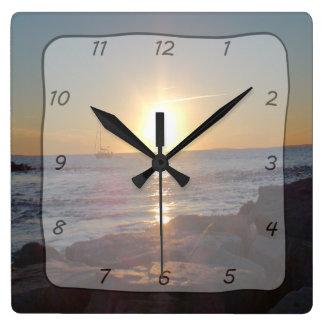 Reloj cuadrado con puesta del sol del océano y la