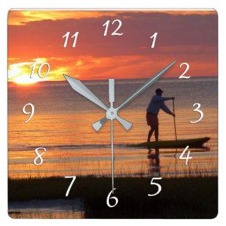 Reloj Cuadrado Hombre en junta de agua en la puesta del sol en la