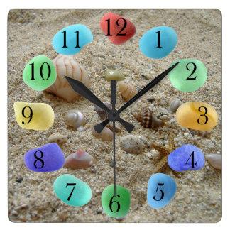 Reloj Cuadrado Seashells en la arena de la playa con el vidrio