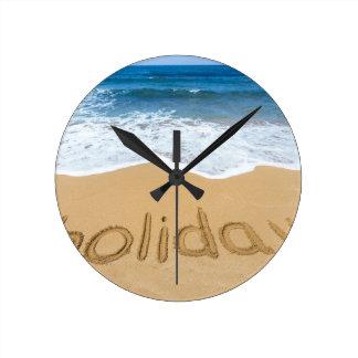 Reloj Redondo Mediano Día de fiesta de la palabra escrito en arena en la