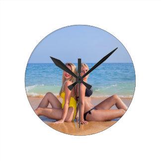 Reloj Redondo Mediano Dos chicas se sientan en la playa cerca de sea.JPG