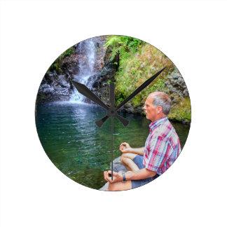 Reloj Redondo Mediano Hombre que se sienta en la roca meditating cerca