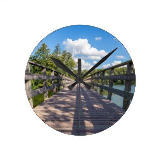 Reloj Redondo Mediano Puente de madera largo sobre el agua de la charca