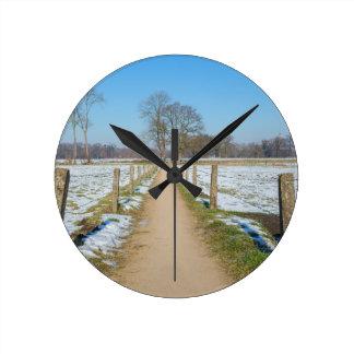 Reloj Redondo Mediano Sandpath entre los prados nevosos en invierno
