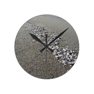 Reloj Redondo Mediano Seashells en la arena. Fondo de la playa del