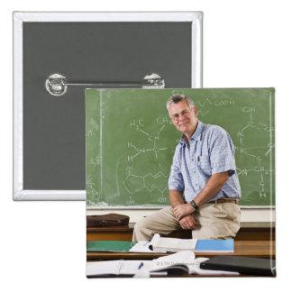 Retrato del profesor que se sienta en el escritori pins