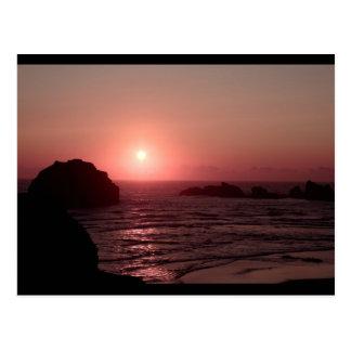 Roca de la cara en la puesta del sol en la postal