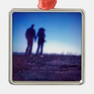 Romantic couple walking holding hands on beach in adorno navideño cuadrado de metal