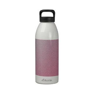 Rosa a la botella de agua azul de la pendiente