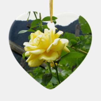 Rosa amarillo del flor en un fondo de la montaña adorno navideño de cerámica en forma de corazón