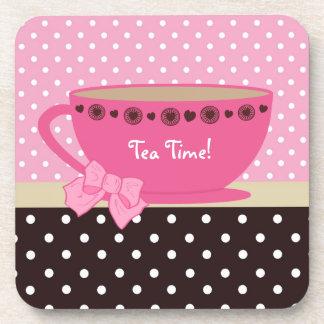 Rosa femenino de la taza de té del tiempo del té y posavasos de bebida