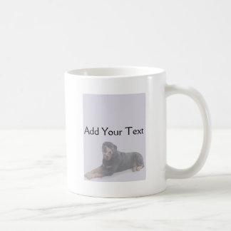 Rottweiler descolorado que coloca en la taza gris