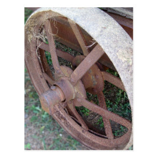 Rueda oxidada del hierro del carro viejo postal