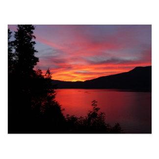 Salida del sol roja hermosa sobre un lago tarjetas postales