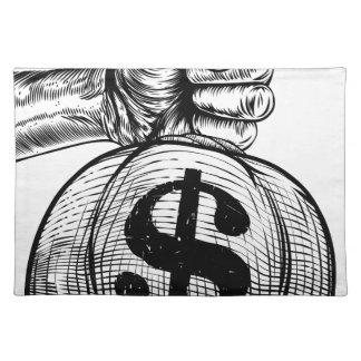 Salvamanteles Mano que sostiene un bolso del dinero del saco de