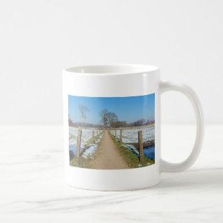 Sandpath entre los prados nevosos en invierno taza de café