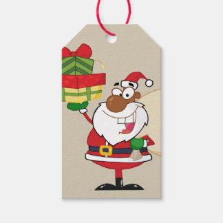 Santa negro que sostiene la etiqueta de papel del etiquetas para regalos