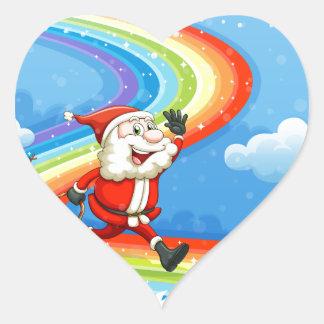 Santa y su trineo que caminan en el arco iris pegatina en forma de corazón