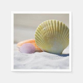 Seashells coloridos en la arena servilleta desechable