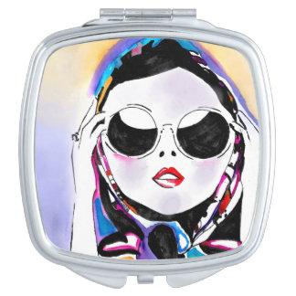 Señora en espejo compacto de las gafas de sol