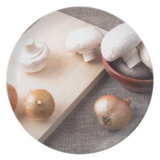 Setas y cebollas crudas del champiñón en la tabla plato de cena