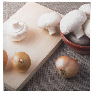 Setas y cebollas crudas del champiñón en la tabla servilleta de tela