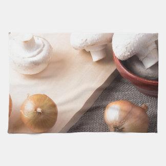 Setas y cebollas crudas del champiñón en la tabla toalla de mano