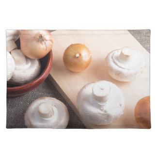 Setas y cebollas crudas del champiñón salvamanteles