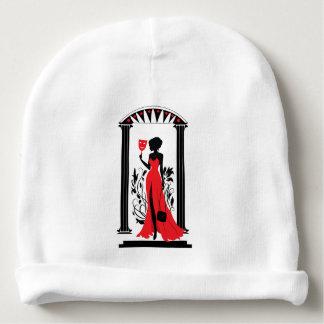 Silueta de la mujer elegante en vestido rojo con gorrito para bebe