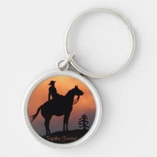 Silueta del caballo y de la puesta del sol del llavero redondo plateado