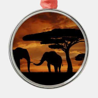 Siluetas de los elefantes africanos en puesta del adorno navideño redondo de metal