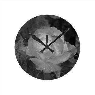 Sola flor color de rosa con las gotitas de agua en reloj redondo mediano