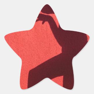 Sombra del perfil de la mujer en la pared roja pegatina en forma de estrella