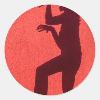 Sombra del perfil de la mujer en la pared roja pegatina redonda