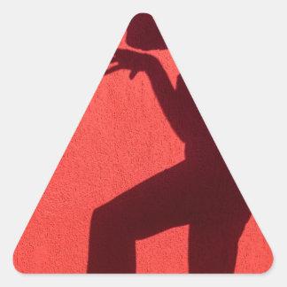 Sombra del perfil de la mujer en la pared roja pegatina triangular