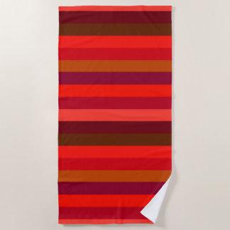 Sombras de la toalla de playa rayada de los rojos