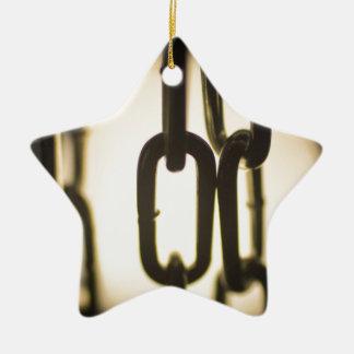 Steel chain links silhouette close-up at night adorno navideño de cerámica en forma de estrella