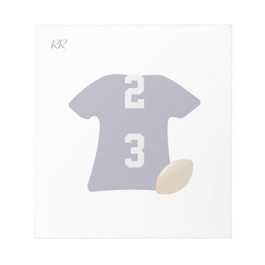 Su camisa del fútbol con la bola en la pequeña bloc de notas