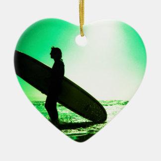 Surfer carrying surfboard in surreal silhouette in adorno navideño de cerámica en forma de corazón