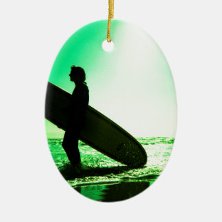 Surfer carrying surfboard in surreal silhouette in adorno navideño ovalado de cerámica