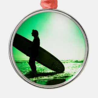 Surfer carrying surfboard in surreal silhouette in adorno navideño redondo de metal