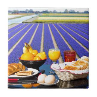 Tabla con la comida y bebida cerca del campo de azulejo de cerámica