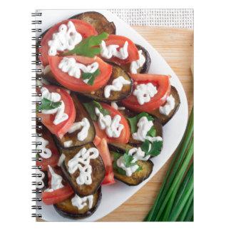 Tabla de cocina con un plato de la berenjena cuaderno