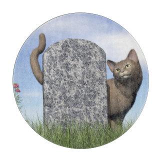 Tabla De Cortar Gato triste cerca de la piedra sepulcral