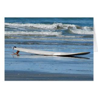 Tabla hawaiana en la playa tarjeta de felicitación