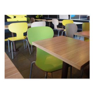 Tablas y sillas de madera en una comida rápida postal