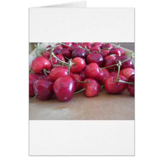 Tarjeta Cerezas maduras rojas en la bandeja de madera