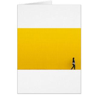 Tarjeta Chica que camina contra la pared amarilla enorme